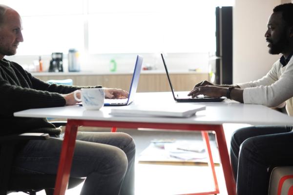 パソコン越しに対談している男性二人