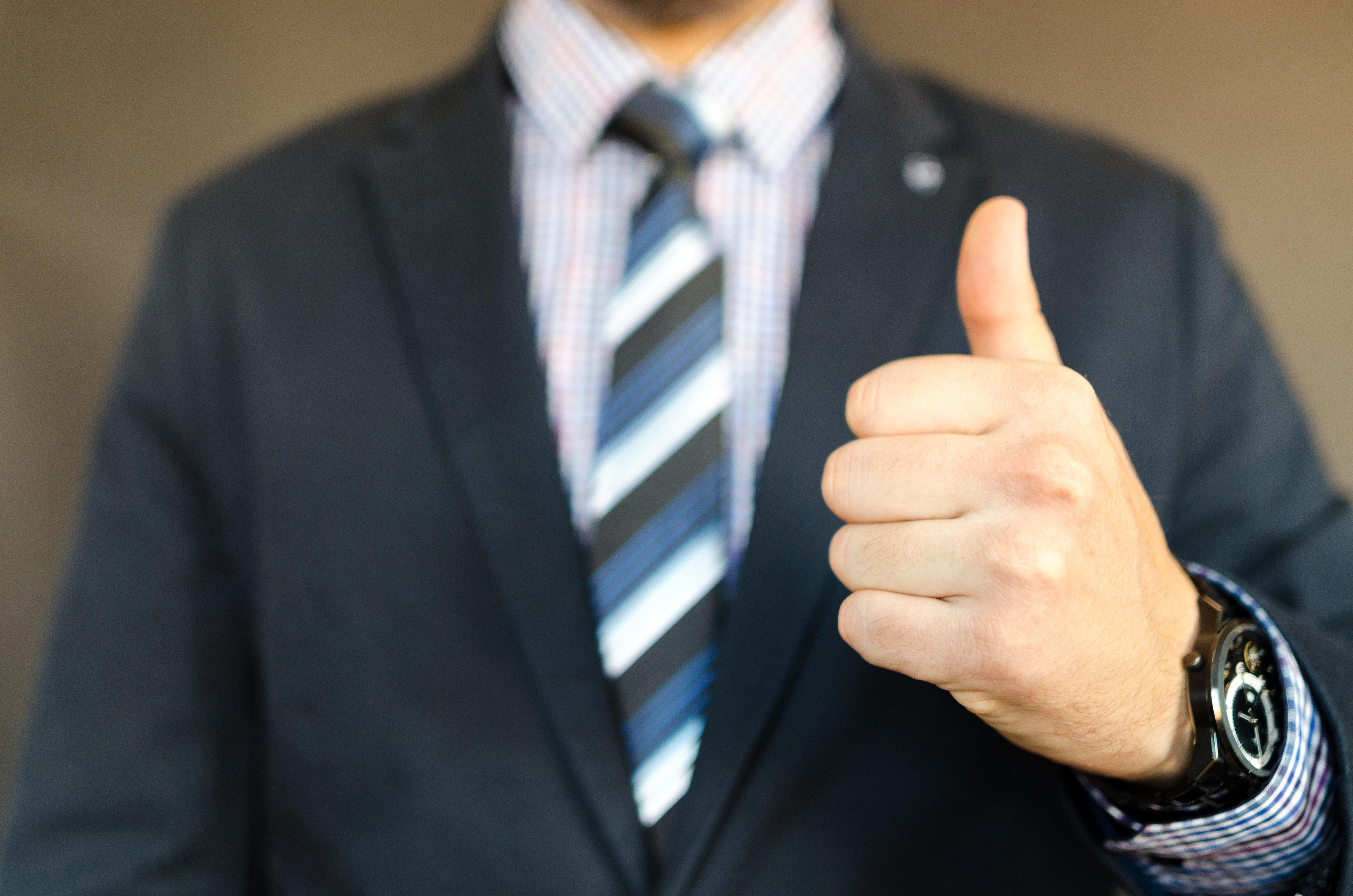 左親指を立てるビジネスマン