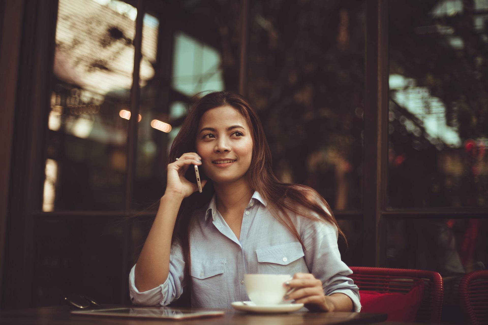 電話する女性とコーヒー