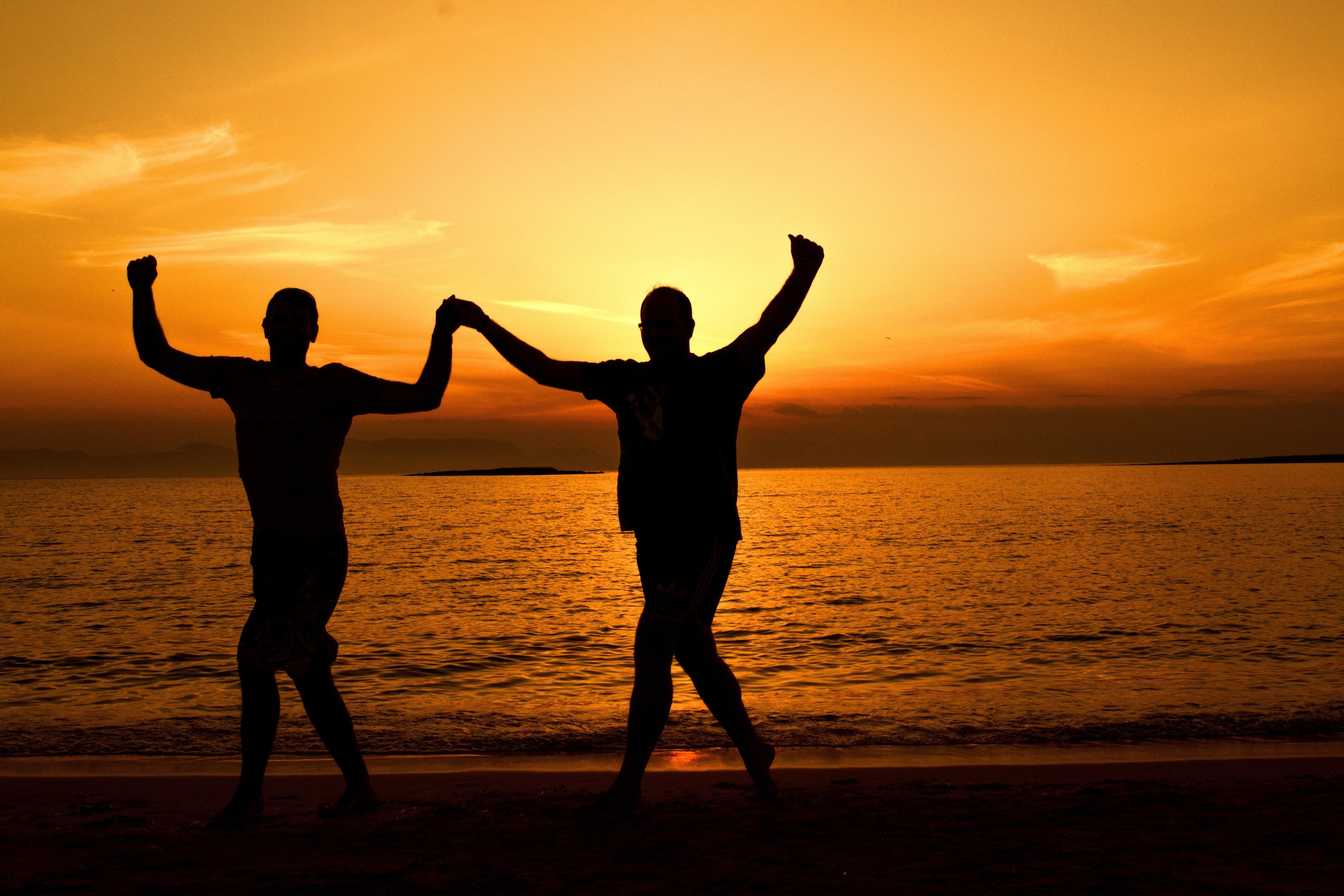 夕日に向かってガッツポーズする2人の男性