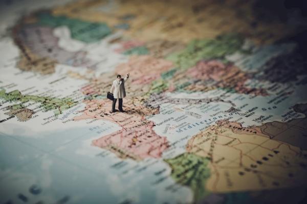 世界地図の上を歩くビジネスマン